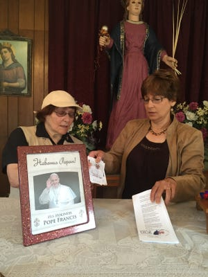 Thelma Bucikowski (left) and her daughter, Marianne Bagliani, both of Vineland, prepare for Saturday's rosary in honor of Pope Francis at St. Barbara Chapel in Vineland.
