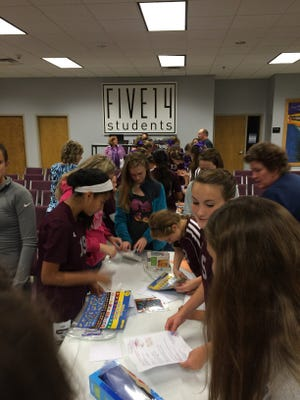 The Lady Dragons and members of the middle school youth group at the First Baptist Church in Dickson work together on making kits for patients.