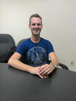 Photo info: Andrew Rivière sits in the Communication Sciences and Disorders department in the basement of Hatcher Hall.