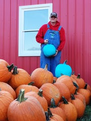 Jason Ladd of Lucky Ladd Farms holds a teal pumpkin. The Eagleville farm hosts fall festivities, including a corn maze and pumpkin patch.