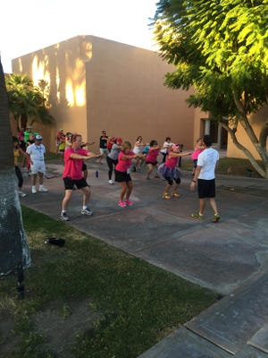 Residents from throughout the Coachella Valley gathered at the Westin Mission Hills Resort Saturday in Rancho Mirage for the eighth Make a Difference Day practice walk. Here, they take part in a stretching session to warm up before the walk.