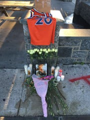 A memorial of flowers, candles and a basketball jersey is set up on Saturday in Sleepy Hollow's Barnhardt Park where Tahj Robinson, 17, was fatally stabbed the previous night. A picture frame of Robinson was also there, which friends penned messages on throughout the evening.