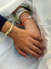 Drew McDermott holds her friend Kennis Cady's hand