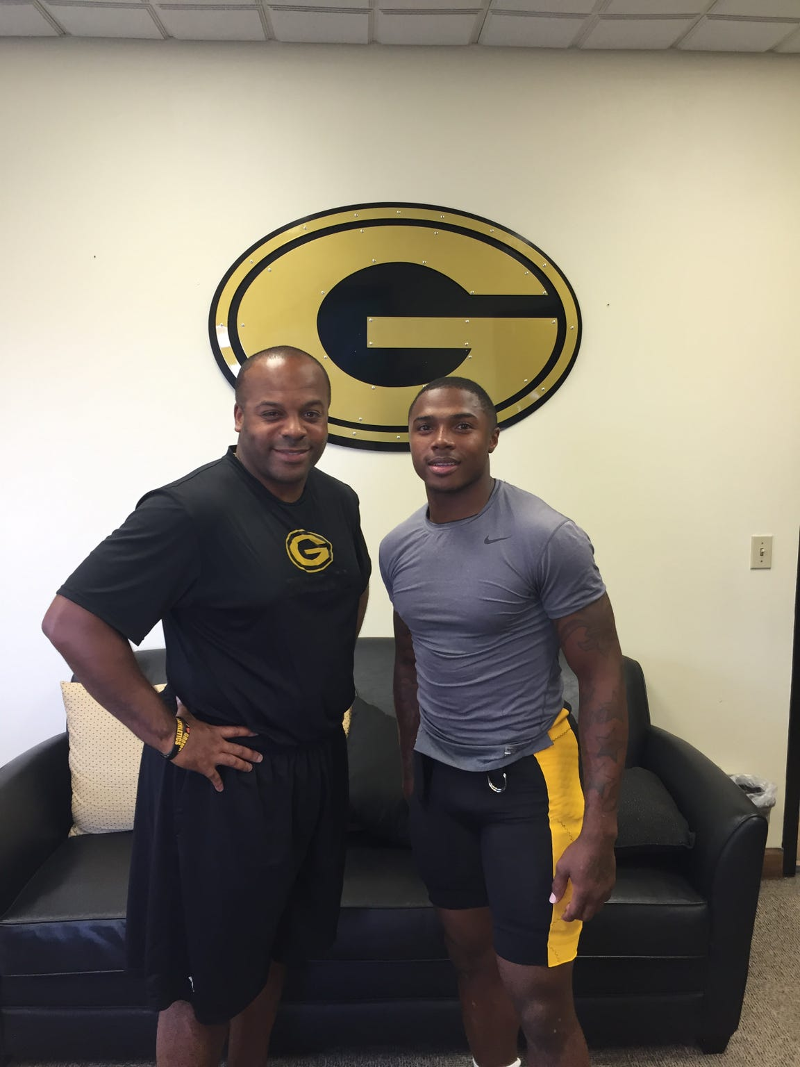 Grambling football coach Broderick Fobbs, left, poses for a photo with running back Martez Carter, right.