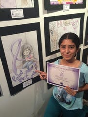 Brisa Perdomo poses with her artwork and certificate from the competition.