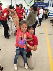 Natalie Phillips, a local audiologist, joined a Starkey Hearing Foundation mission trip to Peru in October. Here, she poses with a young girl she fitted for hearing aids in Piura, Peru.