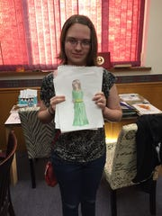 "Dojo Comics student Libby Goble shows a drawing from her novel series ""Maia."""