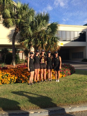 Catholic senior Abby Herrmann, center, holds region trophy with her teammates at Links Golf Club at Sandestin Resort.