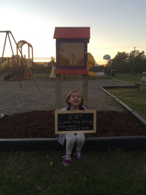 Ellie Zollinger, 7, sits in front of her finished Little Free Library Oct. 21 in Dr. William Henry Park.