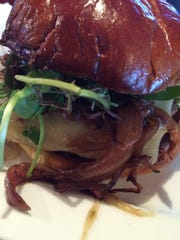The Appleton St Burger is topped with mixed greens,