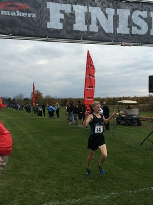 Lansing Catholic's Ethan Markey crosses the finish line at the Division 3 cross country regional at Uncle John's Cider Mill. Markey was the individual winner and helped the Cougars capture the team title.