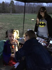 Blaze Parker facepaints Zoey Clem, a member of the Miller Memorial Baptist Church in Augusta Springs, as part of the Harvest Blessings Party. Brooklyn Wolfe is dressed as Batgirl.
