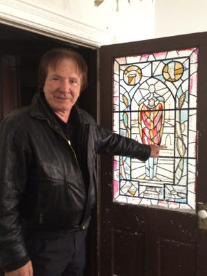 George Pan-Andreas points to a stained glass window inside the former Sisters of the Holy Nativity Convent at 101 E. Division St. downtown. Pan-Andreas, a Hollywood actor, wants to completely restore the burned block-long building, which has been vacant since 2000.