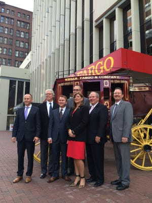 Local officials celebrate the announcement of a Wells Fargo museum on Walnut Street including, from left: assistant city manager Matt Anderson; Mayor Frank Cownie; Financial Center owner Mark Buleziuk; Greater Des Moines Partnership CEO Jay Byers; Area president of Wells Fargo Bank Marta Codina; Greater Des Moines Partnership President Gene Meyer; and Wells Fargo lead regional President Don Pearson.