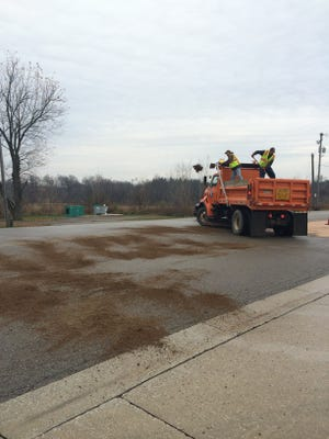 Crews apply sand to oily pavement near the site of a semi-truck crash this morning.