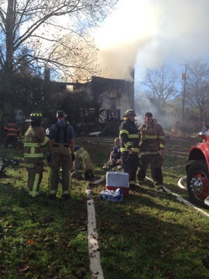 Weary firefighters try to catch a quick break in Eagleville after battling the blaze for hours.