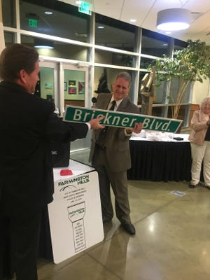 Former Mayor Barry Brickner accepts a personalized street sign from City Manager Dave Boyer.