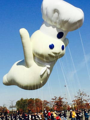 Tee hee! Pillsbury Dough Boy soars, preparing for Macy's Thanksgiving Day Parade.