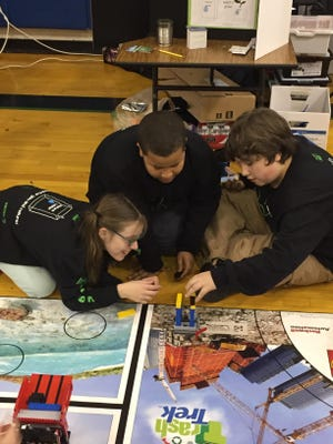 Nazareth Hall Middle School students Sarah Kimball, Boston Wynter and Dante Apollonio test their LEGO robot before their match at the FIRST LEGO League Event at Spry Middle School.