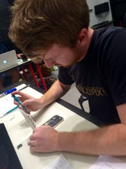 Justin Murphy works on a device at the uBreakiFix store at Coconut Point in Estero.