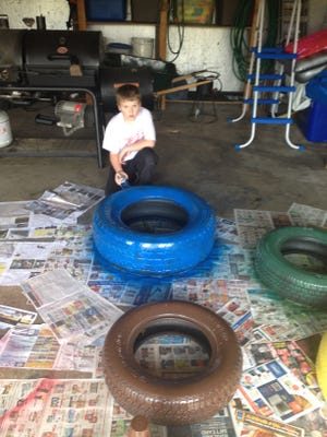 Unioto student Rocky Rinehart paints a tire as part of the project to turn old tires into a DIY project.