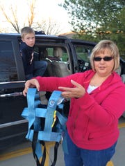 Kelly Ramus holds a vehicle harness paid for by Medicaid used to keep her son, Treyner, in his seat while traveling.  Treyner slips out of the standard seat belt. Items like the harness provide safety and Kelly Ramus has concerns whether they will be covered if private companies take over the program's management.