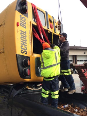 Keford Towing's Brandon Allen (left) and Will Greulich tie on straps before the bus can be lifted.