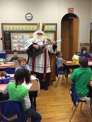Father Jeremy Miller dressed up as Saint Nicholas and sang songs with students Friday at St. Peter's Elementary and Montessori school.