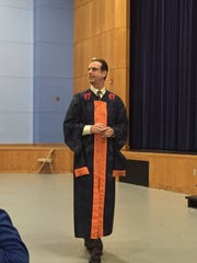 Michael Delaney, principal of Carolina High School in Greenville, wears a graduation gown signed by seniors while speaking to the senior class on Dec. 7, 2015.