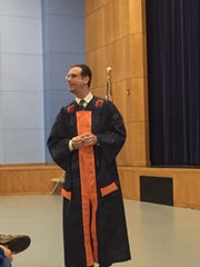 Michael Delaney, principal of Carolina High School in Greenville, wears a graduation gown while speaking to the senior class on Dec. 7, 2015.
