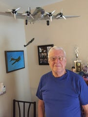 Robert Lopiano stands beneath a model of the B-17, the plane he served on during World War II.