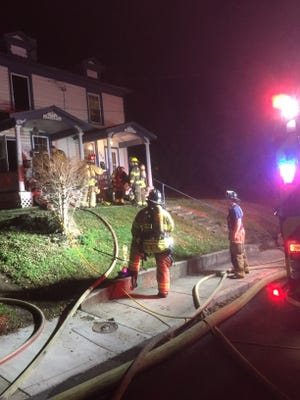 After a fire at 306 Sunnyside Street in Staunton, fire crews work to make the scene safe for the residents of 304 as neighbors watch.