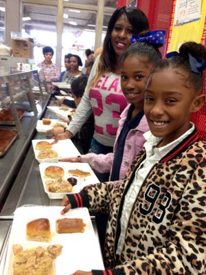 Tiffany Dotson and her daughters Alexia Dotson and Arianna Johnson grab Christmas lunch Wednesday in the Acadian Elementary cafeteria.