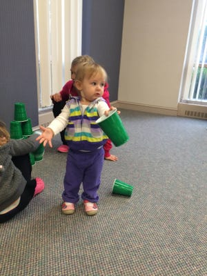 Cammie Flakowitz, 1, helps her mom and older sister pick up green cups for a game at the Ocean Pines Library.