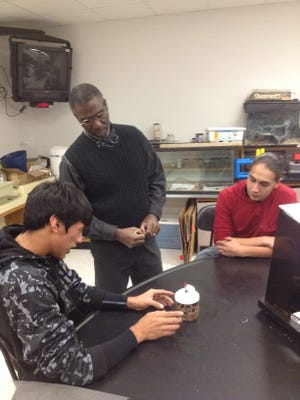 Mescalero Apache sophomore Matias LaPaz, left, demonstrates the principle of microbe-generated electricity to his teacher Nate Raynor and senior Albert Valdez, right.