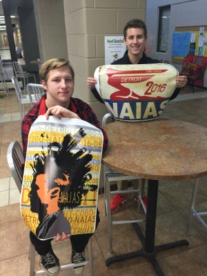 From left, Donovan Mattson and Bryen Gatt show off their posters that were picked to be showcased in the Detroit Auto Show in January.