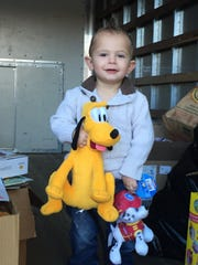 Tommy Dumanski, 2, with a few of the toys that were donated to CHOP.
