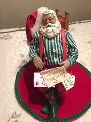 Santa is snoozing after reading a pile of letters from children.