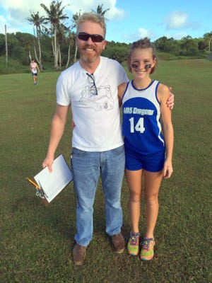 Andersen Dragons' coach Nathan Mapson and unbeaten Tabetha Boldt at the IIAAG All-Island Middle School Cross Country Meet at the Harvest Christian Academy field Friday, Dec. 18. Boldt finished first in 9:24.