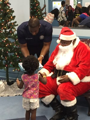 Mayor Andrew Gillum and Santa, played by Bethel AME Community Development Corporation executive director Darryl Jones, passed out gifts to local children at the Oliver Hill Housing Authority Apartments on Wednesday.