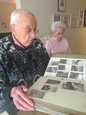 Fred Bernstein flips through a scrapbook at his Fox Run home in Novi with his wife, Sandra, sitting nearby.