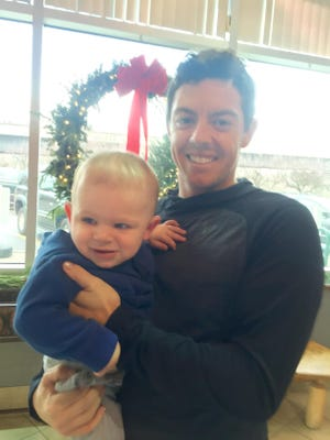 Pro golfer Rory McIlroy holds toddler Cashel Mooney during a visit to Midtown Athletic Club.