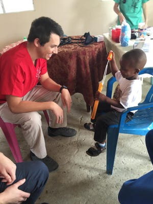 SUU student Jared Wilson plays with a child in the Dominican Republic during a trip to help local doctors treat patients over the Christmas break.