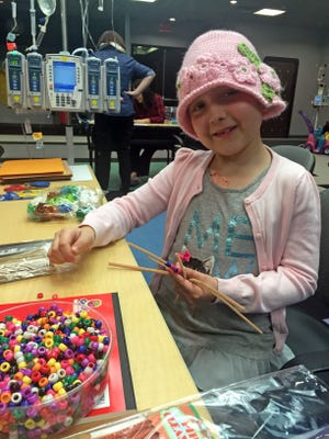 Seven-year old Belle Ferretti fills her backpack with toys, art supplies and stuffed animals for her trips to the hospital. Since her diagnosis last June, that is where she has spent most of  her days.