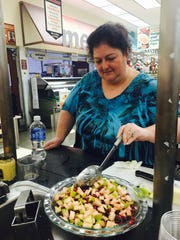 Marlton Women's Club member Debbie Price mixes pear and pomegranate salsa at a culinary workshop at Marlton ShopRite