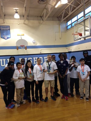 Four-time Olympian Joetta Clark Diggs poses with Asbury Park middle school students and teachers
