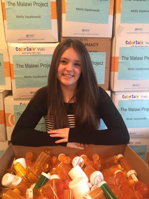 Morris Catholic High School sophomore Molly Szpakowski with 8,900 empty pill bottles she collected for reuse in the African nation of Malawi.