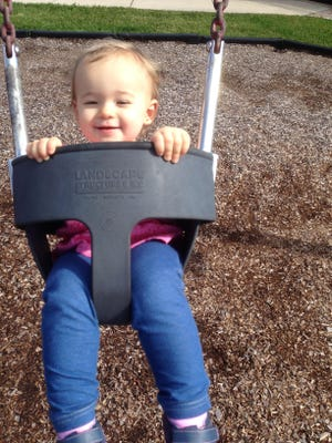 Isabella swings while enjoying a day on the playground with her daddy.