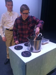 Jacob Turner, who plays Mr. Wonka and Bryce Vrooman, who plays Grandpa Joe, rehearse a scene from the show using the props the students made.