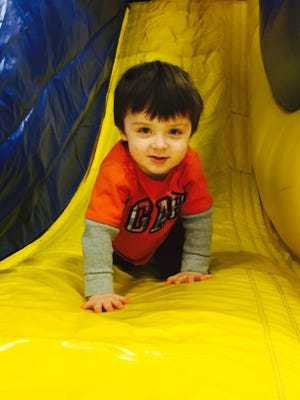 Cameron Grebner, 3, rides an inflatable slide at the 2016 Victor Winterfest.
